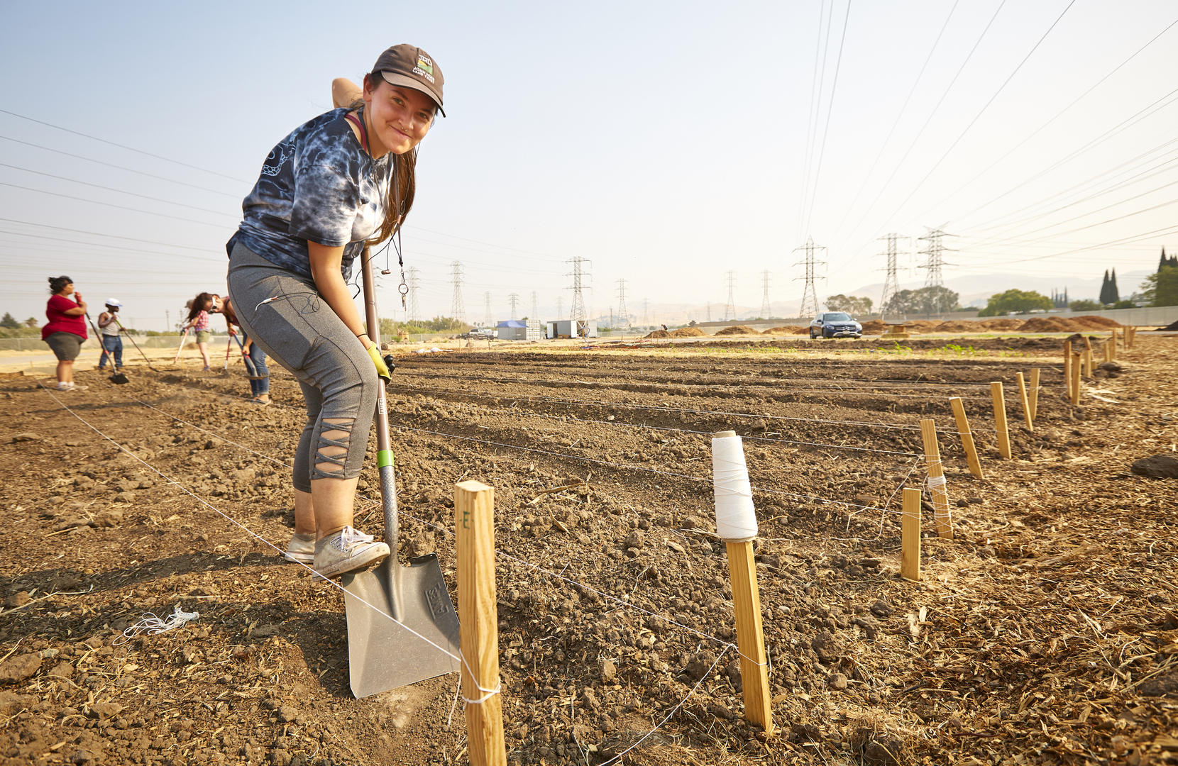 Young woman shoveling soil in an open field, preparing for planting.